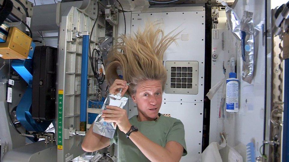 Астронавт NASA Карен Найберг демонструє, як мити голову в космосі