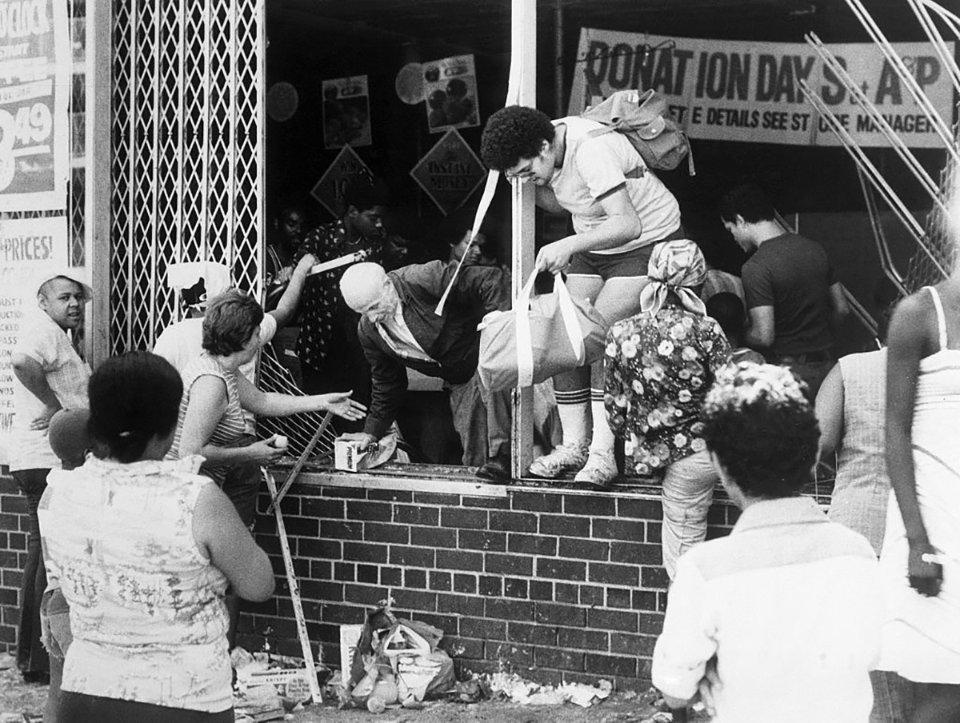 Мародеры вылезают через окно разграбленного супермаркета A&P в Бронксе